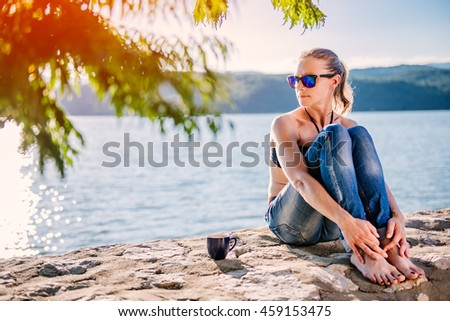 Woman with sunglasses wearing black bikini and jeans sitting on the stone dock and drinking coffee