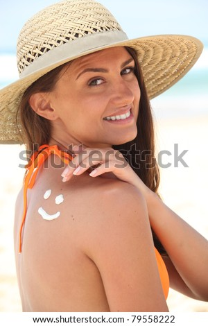 woman with sunscreen on the beach wearing a hat - stock photo