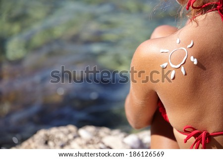 Woman With Suntan Lotion At The Beach In Form Of The Sun  - stock photo