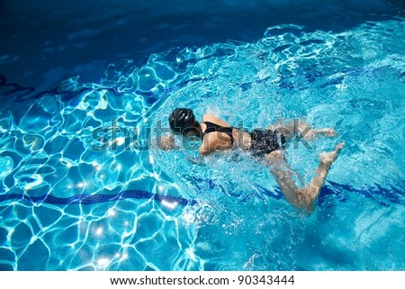 woman with swimsuit swimming on a blue water pool - stock photo