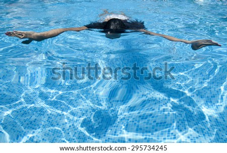 Woman with swimsuit swimming on a blue water pool. Copy space. - stock photo