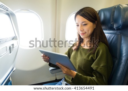 Woman with tablet computer in airplane