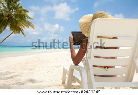 Woman with tablet computer on the beach sitting in the deck chair - stock photo