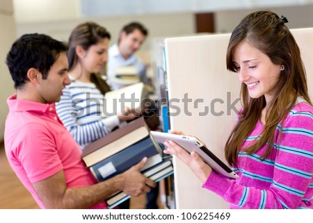 Woman with tablet computer reading an e-book and friends carrying heavy books - stock photo