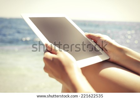 Woman with tablet pc at the beach. Vintage photo. - stock photo