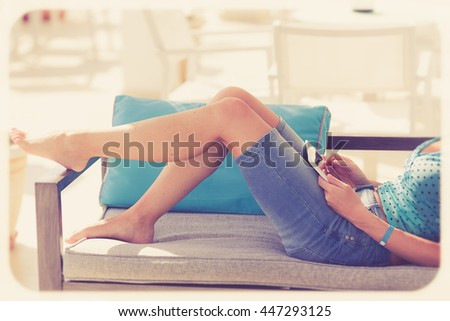 woman with tablet relaxing on the terrace in luxury hotel. Vintage style. - stock photo