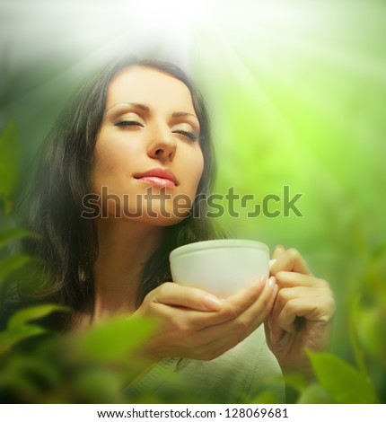 Woman with tea cup on background of blurred green leaves - stock photo
