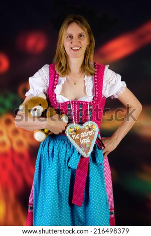 Woman with teddy and gingerbread at fun fair - stock photo