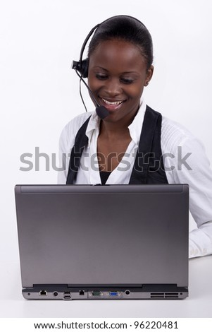 Woman with telephone headset and a laptop, serving a customer telephonically. - stock photo