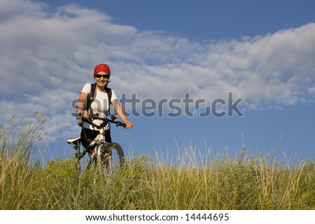 woman with the bicycle on grass meadow