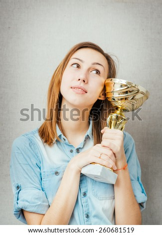 woman with the cup winner. isolated on gray background - stock photo