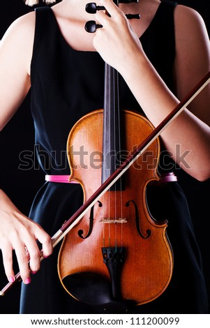 Woman with the violin over black background - stock photo