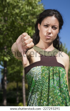 woman with thumb down in exterior background - stock photo