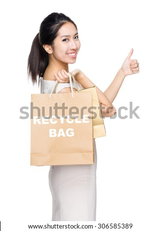 Woman with thumb up gesture and holding shopping bag for showing recycle bag