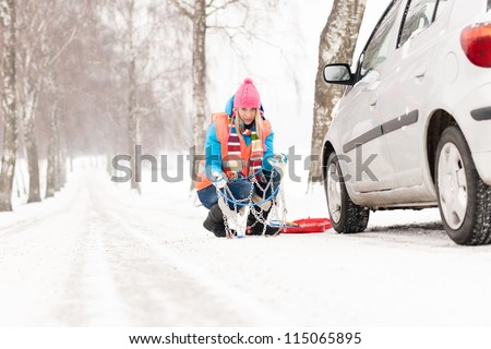 Woman with tire chains car snow breakdown smiling fixing winter - stock photo
