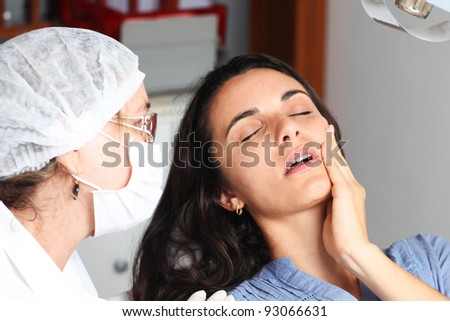 Woman with toothache at the dentist - stock photo
