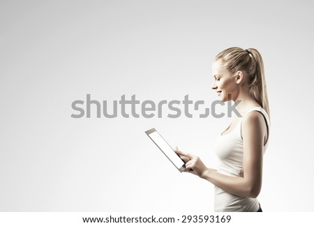 woman with  touch pad on gray background - stock photo
