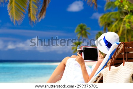 woman with touch pad on tropical beach vacation - stock photo