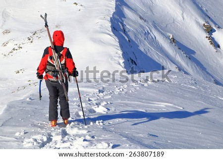 Woman with touring skies on the backpack descending snow covered ridge in sunny winter day - stock photo