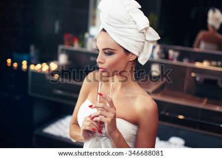 Woman with towel holding glass of champagne in bathroom - stock photo