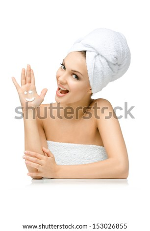 Woman with towel on head shows cream smiley on palm, isolated on white. Concept of healthcare, beauty and youth - stock photo