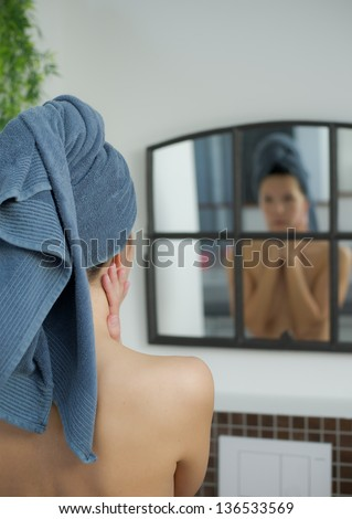 woman with towel on her head looks into mirror