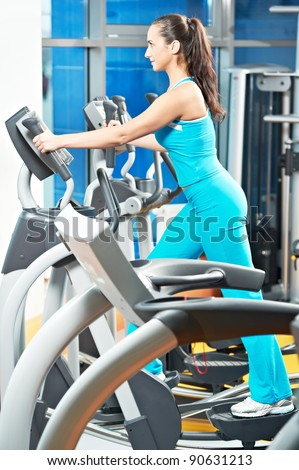 woman with training equipment at fitness club gym doing exercises for back muscles - stock photo