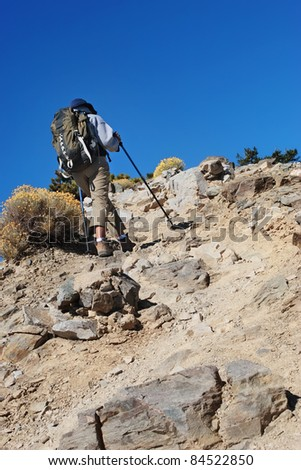 Woman with trekking poles and backpack hiking a rocky mountain - stock photo