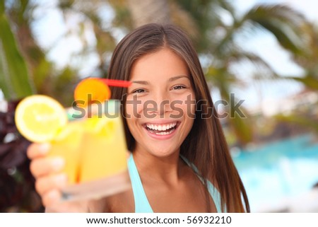 Woman with tropical drink by the pool tropical resort. Beautiful multiracial Asian / Caucasian young woman in bikini during summer holidays. - stock photo