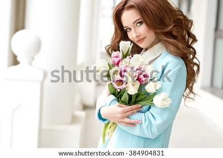 Woman with tulips. Beautiful woman with flowers. - stock photo