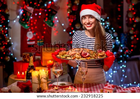 Woman with turkey garnished with potato and garnet dressed with Christmas hat on festive light background - stock photo