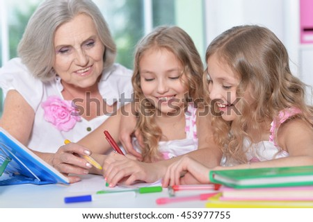 woman with tweenie   girls doing homework - stock photo