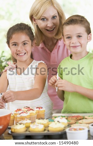 Woman with two children in kitchen decorating cookies smiling - stock photo