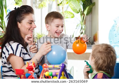 woman with two children playing with balloons in home interior laughter - stock photo