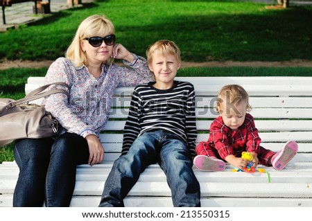 woman with two children sitting on the bench - stock photo