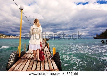 Woman with umbrella and bag at hands walking on wooden sea footbridge - stock photo