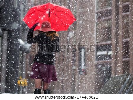 Woman with umbrella from behind walk on street - stock photo