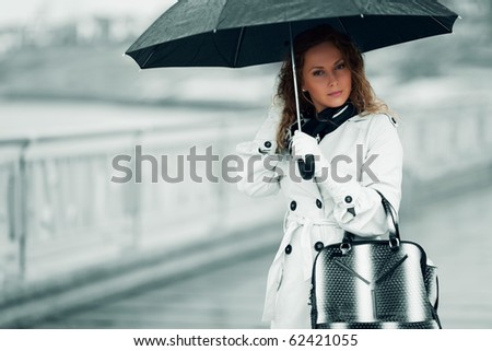 Woman with umbrella in the rain. - stock photo