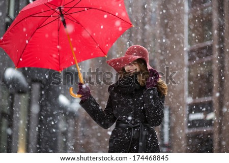 Woman with umbrella on snowy street at day - stock photo