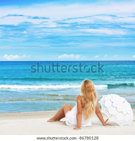 Woman with umbrella on the tropical beach - stock photo