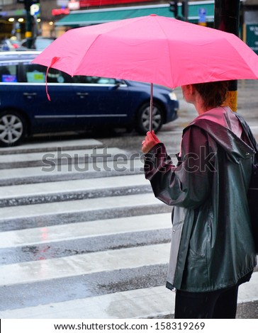 Woman with umbrella waiting in the rain