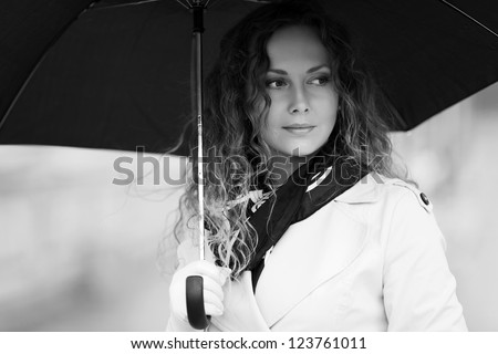 Woman with umbrella walking on the street - stock photo