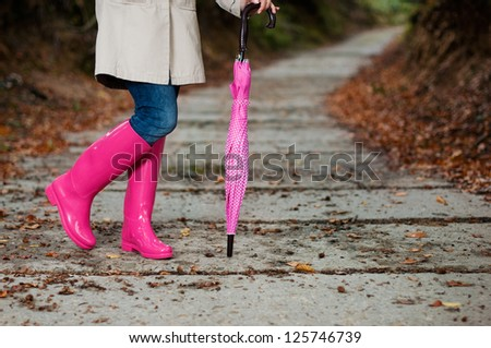 Woman with umbrella wearing rubber boots