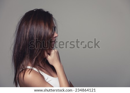 Woman with untidy long brown hair standing sideways with the hair hiding her face, on grey with copy space - stock photo