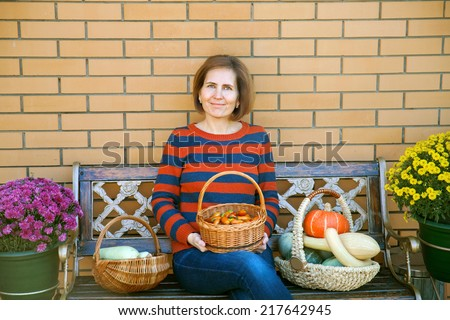 woman with vegetables in wicker baskets sitting on the bench in the courtyard - stock photo