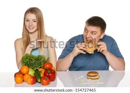Woman with vegetables pointing at a man eating fast food, against white background - stock photo