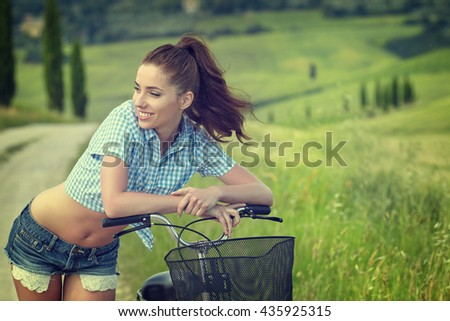 Woman with vintage bike in a country road.