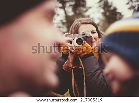 Woman with vintage camera is taking picture of her little son and husband outdoor - stock photo