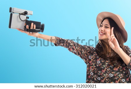 Woman with vintage video camera over colorful background - stock photo