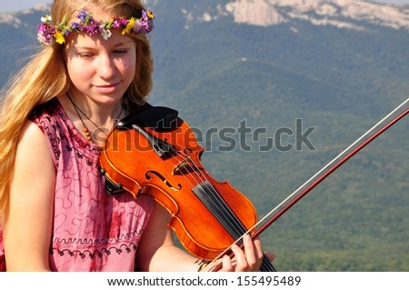 woman with violin in the mountains  - stock photo